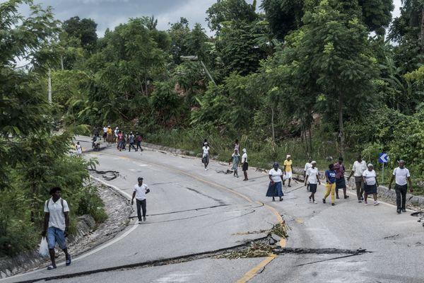 Des badauds sur une route dévastée par le séisme qui a eu lieu samedi 14 août, à côté de Camp-Perrin en Haïti.