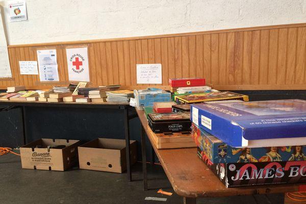 Sur une table, des jeux de société, des livres, des journaux sont à disposition des personnes accueillies.