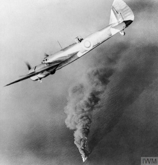 Un Bristol Blenheim du 107 Squadron de la RAF au-dessus d'un navire britannique en flammes, après avoir été attaqué par les Allemands (photo non datée).