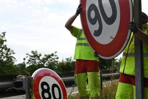 Les employés de la Direction interdépartementale des routes de l'Est remplacent un panneau de limitation à 90 km/h par un panneau 80 km/h, à Wittenheim (Haut-Rhin), le 29 juin 2018