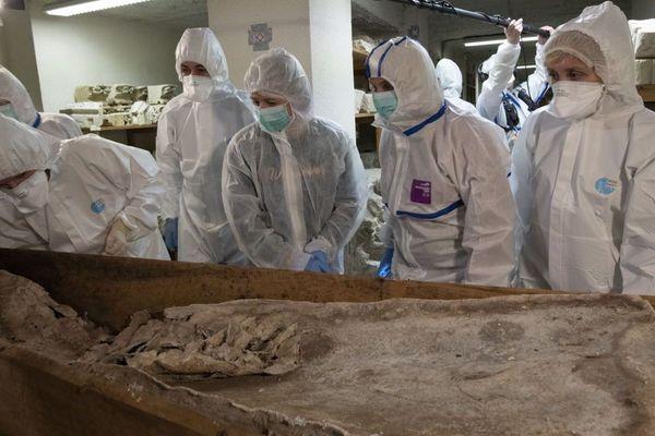 L'équipe scientifique au-dessus d'un cercueil. Ils cherchent à savoir si la dépouille est celle de Michel de Montaigne.