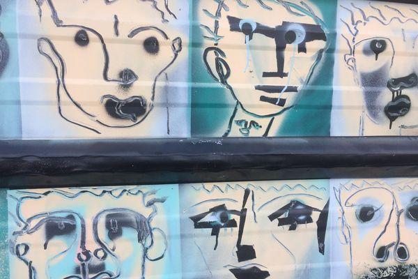 Sur la tôle ondulée, les visages symbolisent les habitants en devenir