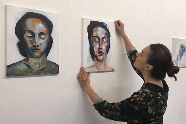 """Albane Dela accroche les 7 oeuvres qu'elle propose à l'exposition """"Jeunes artistes"""" de la galerie Art'Course"""