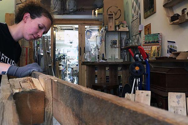 Taana a créé avec son compagnon David l'association Wood Stock Project à Montpellier. Elle s'apprête à démonter une palette en bois pour fabriquer un meuble.