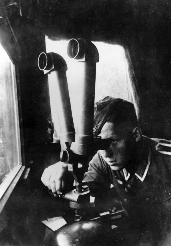 Un soldat allemand observant à travers un double télescope depuis une batterie du front occidental, en octobre 1940.