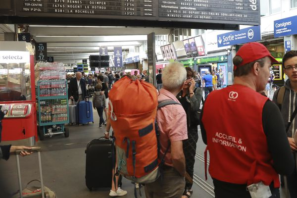 Des passagers se renseignent auprès du personnel de la SNCF après les perturbations en gare Montparnasse à Paris, dues à des problèmes techniques sur les lignes.