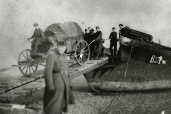 """Soldats allemands déchargeant d'une barge, une charrette, sur une plage, près de Boulogne-sur-Mer, lors de la préparation de l'opération """"Seelöwe""""."""