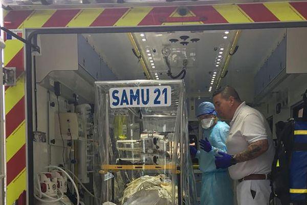 Les équipes auprès d'un patient, dans une ambulance de transfert.
