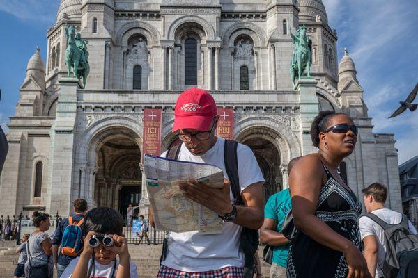 Des touristes photographient le Sacré-coeur, à Paris.