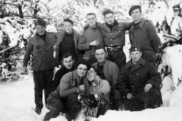 En Silésie pendant la captivité. Paul Aubé est assis, pantalon et gants couverts de neige, entouré de compagnons inconnus