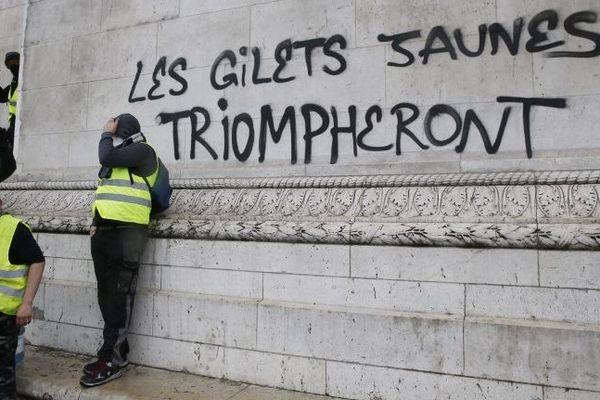 Des manifestants gilets jaunes devant un tag sur l'Arc de triomphe, le 1er décembre 2018.