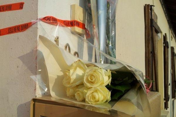 Des riverains ont déposé des oeillets roses et des roses blanches devant l'habitation.