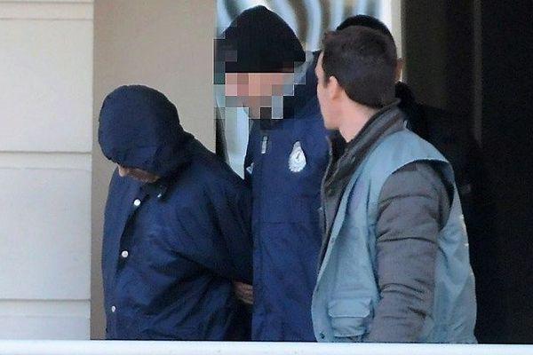 Le suspect sort de son immeuble encadré par les policiers - 2012