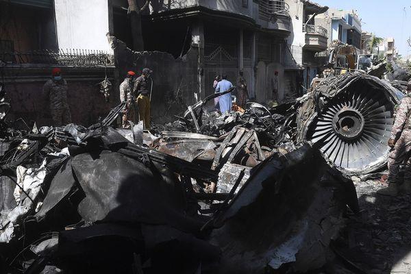 Du personnel de sécurité à côté de l'épave d'un A320, deux jours après que celui-ci se soit écrasé sur les maisons d'un quartier résidentiel de Karachi, au sud du Pakistan, le 22 mai 2020.