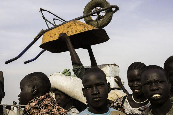 Camp de protection des civils de l'ONU, Bentiu, Soudan du Sud, 2015. Des hommes attendent de pouvoir emporter des vivres pendant une distribution de nourriture au sein du camp qui accueille plus de 110 000 personnes déplacées. Ceux qui fuient les combats et l'insécurité alimentaire pénètrent dans les camps de protection des civils après des semaines ou des mois cachés dans la brousse. © Dominic Nahr pour Médecins sans frontiers