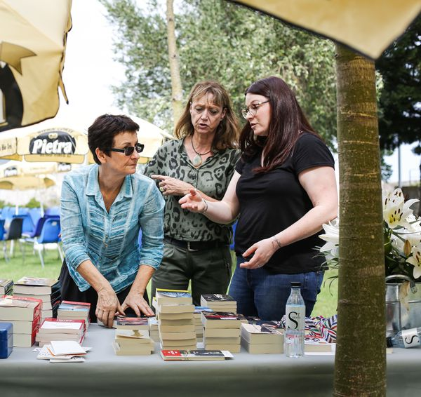 Lory Massey à la manoeuvre derrière son stand de livres, durant un festival littéraire bastiais