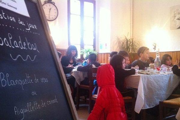 Les élèves de l'école mangent au restaurant du village, au milieu des clients.
