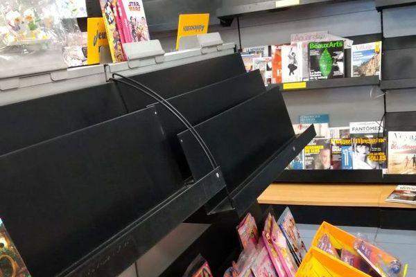 Présentoir vide dans un magasin de presse