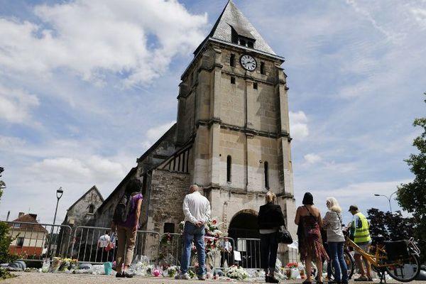 Quelques personnes se recueillent le 28 juillet devant l'église de Saint-Etienne-du-Rouvray, en Seine-Maritime.