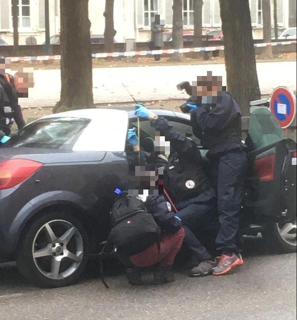 La police scientifique travaillant sur le véhicule ayant reçu un impact de balle.