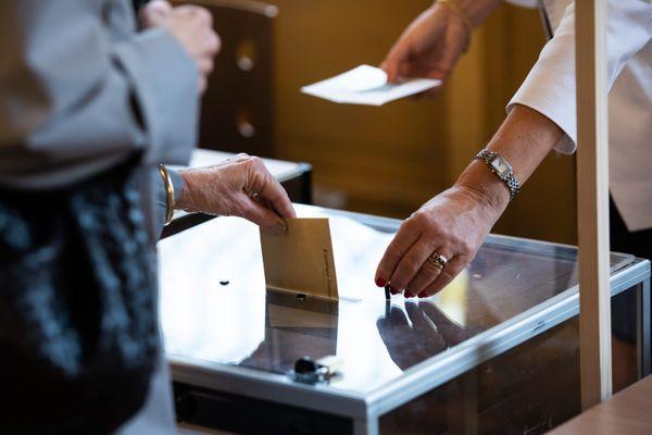 Une électrice glisse son bulletin de vote dans une urne - Photo d'illustration