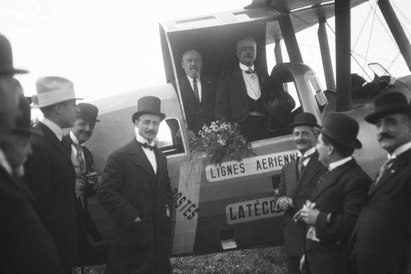 """Souvenir de la fête aérienne organisée en 1921, à Montaudran, à l'occasion de la """"Décade latine"""". Le maire de Toulouse, Paul Feuga (à droite) pose à bord d'un appareil des Lignes Aériennes Latécoère après une excursion au-dessus de la ville. Sur la piste, Pierre-Georges Latécoère avec son chapeau haut-de-forme."""