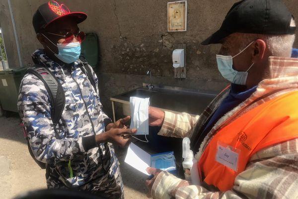 Guy travaillant au Relais Orléanais donne un masque et du gel hydroalcoolique aux bénéficiaires avant de récupérer leurs sacs.