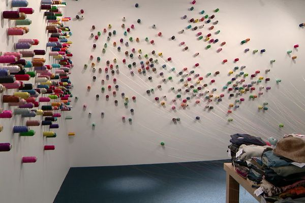 Les vêtements recousus sont ensuite déposés sur une table et reliés à une bobine accrochée au mur.