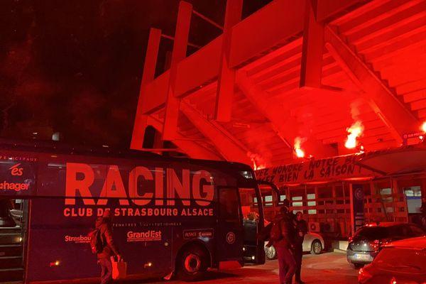 """Le bus des joueurs du Racing accueilli par des fumigènes rouges et une banderole """"Vous avez bien honoré notre blason, finissez bien la saison""""."""