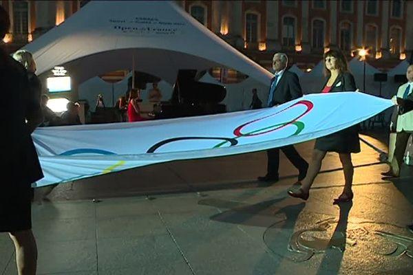 Le drapeau des Jeux Olympiques porté devant la Place du Capitole