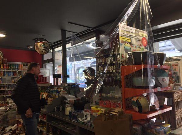 Dans cette supérette, une bâche en plastique sépare les clients du vendeur. Les masques, gants et gel ont été livrés ce mardi seulement, après deux semaines de confinement.