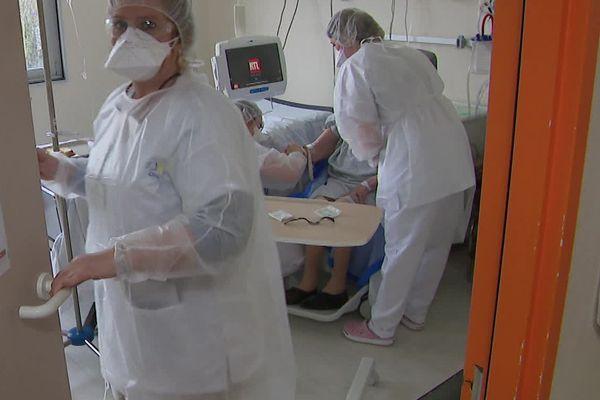 Charlotte, surblouse et lunette de protection avant d'entrer dans une chambre dans ce service qui accueille les patients Covid.