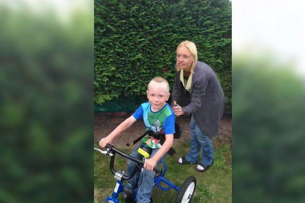 Daven, tout sourire sur son vélo, aidé par sa maman.