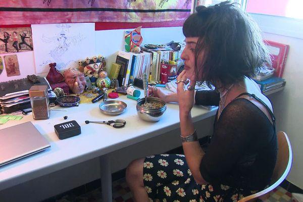 Attablée à son bureau/table dans sa chambre universitaire, Anita a un budget de 3 euros par jour pour se nourrir.
