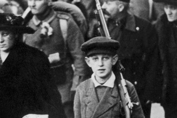 Photographie d'un enfant portant le fusil de son père lors de la mobilisation en Autriche en août 1914.