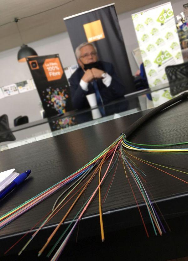 Un faisceau de fibres optiques avec à l'arrière-plan Marc Maouche, délégué régional Orange-Normandie