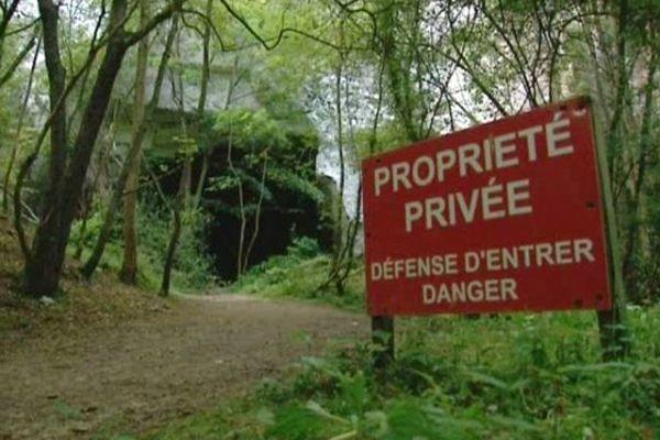 Panneau d'interdiction devant l'une des entrées de la grotte de Caumont