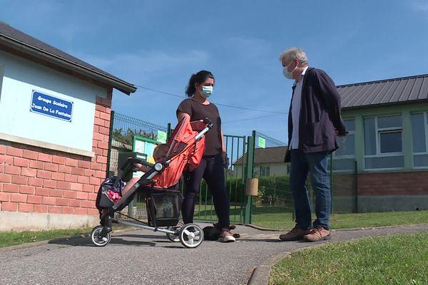 Le maire de la commune Aubenton, Bernard Gréhant, et une maman d'élève devant l'école du village