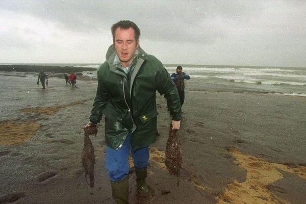 Un homme transporte les cadavres d'oiseaux de mer enduits de mazout, le 26 décembre 1999 sur la Plage Valentin à Batz-sur-Mer, recouverte par le mazout de l'Erika.