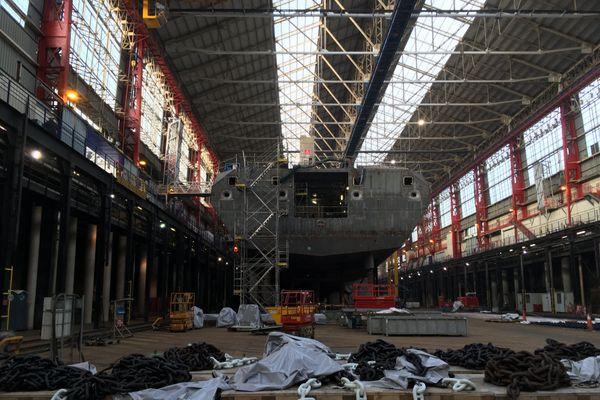"""Dans la forme du chantier naval de Lorient, chaque FREMM a été assemblée par anneaux. Ici, l'un des """"tronçons"""" de la frégate Lorraine en février 2020."""