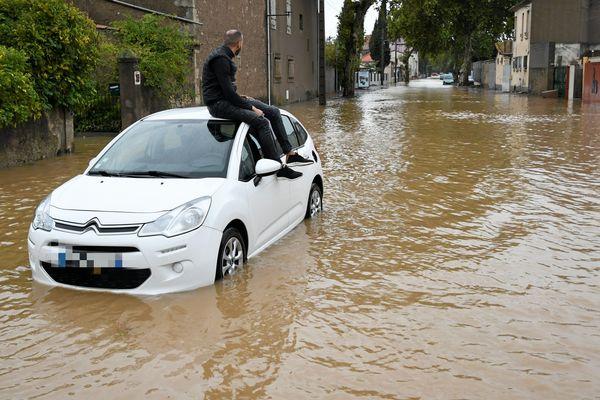Un automobiliste isolé sur le toit de sa voiture dans les rues inondées à Béziers lors des intempéries du 23 octobre 2019.