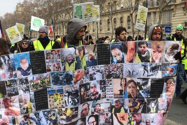 """Une banderole tenue par des gilets jaunes pour dénoncer les violences policières, en plein """"acte 10"""" du mouvement à Paris."""