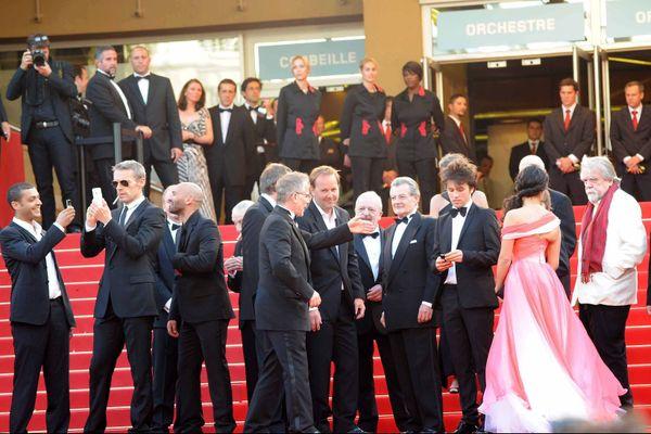 """L'équipe """"Des hommes et des dieux""""  de Xavier Beauvois à Cannes en 2010, lors de la montée des marches.Michael Lonsdale est à droite."""