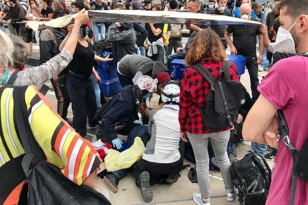 """Une femme blessée à terre secourue par les """"street medics"""" lors d'un rassemblement des gilets jaunes samedi 16 mai place de la Comédie à Montpellier."""