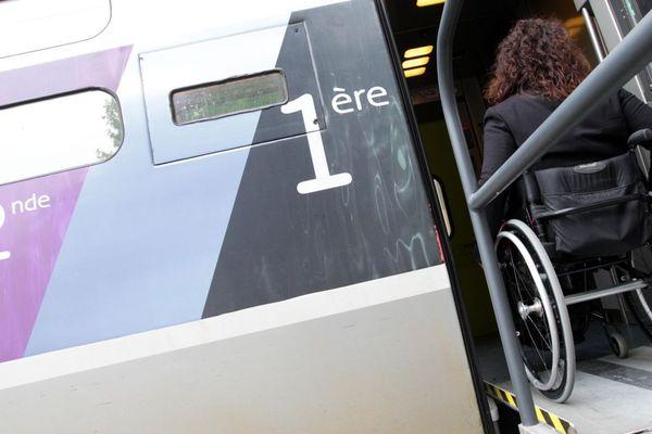 Une personne handicapée monte dans un train avec son fauteuil roulant