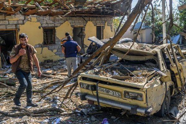 Des résidents locaux se tiennent près d'une voiture endommagée à Barda, en Azerbaïdjan, près de la capitale contestée de la province du Haut-Karabakh, Stepanakert, le 9 octobre 2020, alors que l'Azerbaïdjan et l'Arménie tiennent leurs premiers pourparlers de haut niveau après près de deux semaines d'affrontements.