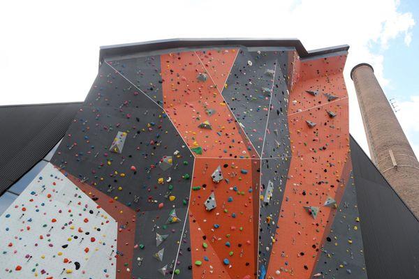 Le mur extérieur du Climbing Mulhouse Center culmine à 25 mètres de hauteur, à côté des cheminées de l'ancien site industriel DMC.