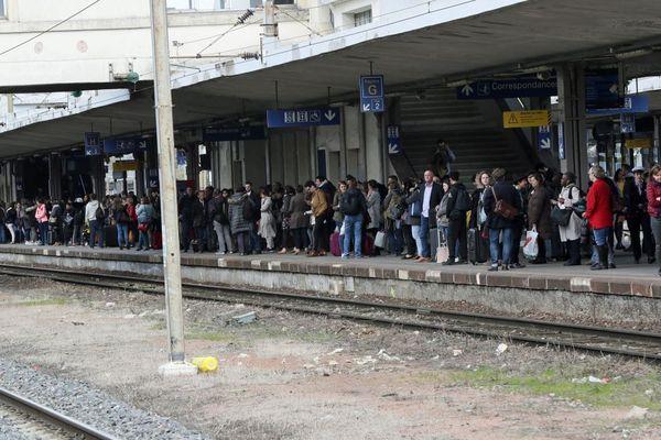 Les voyageurs attendent un train pour Strasbourg en gare de Mulhouse au soir du premier jour de grève à la SNCF.