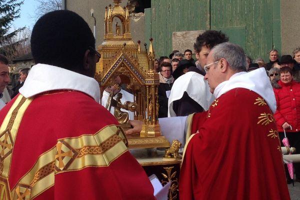 fidèles et religieux sont rassemblés autour de la relique du sang du Christ à Neuvy-Saint-Sepulchre