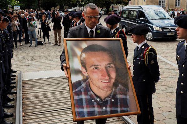 Un homme porte une photo du caporal Arthur Noyer, lors de ses funérailles, en septembre 2018.